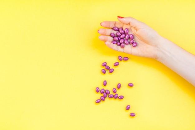一握りの紫色の丸薬を持つ女性の手