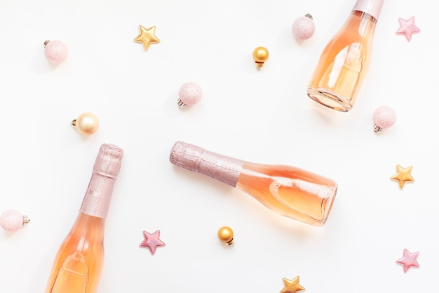Бутылки розового шампанского на белом фоне