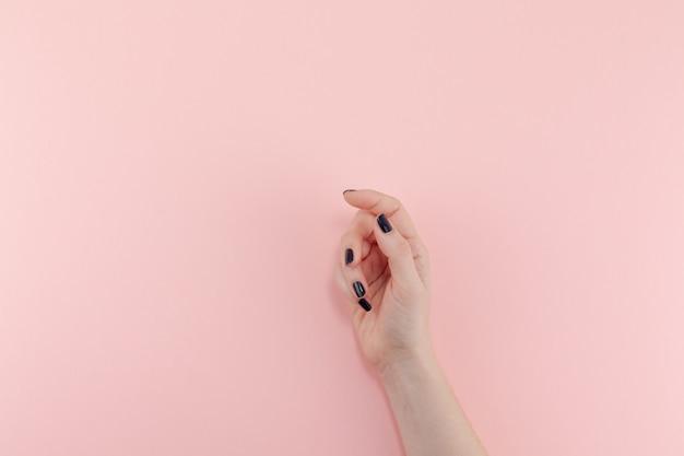 黒のマニキュアと女性の手
