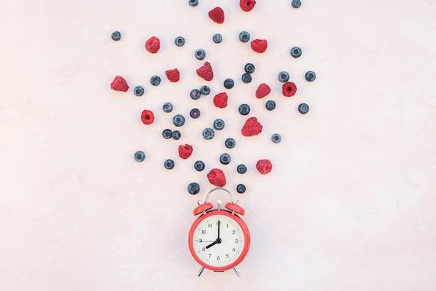 ベリーと赤い目覚まし時計のコンポジション