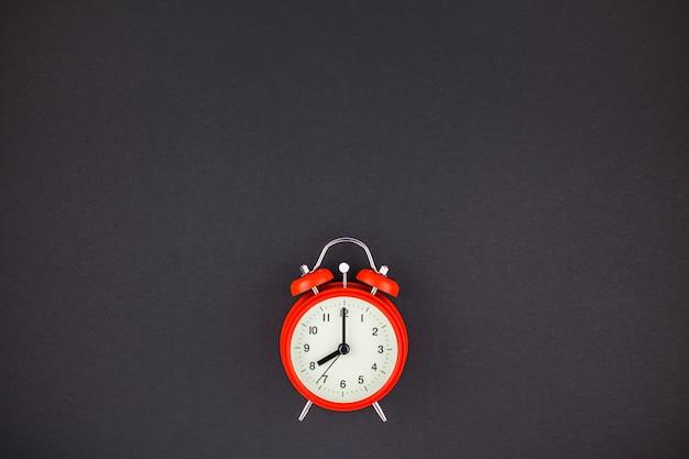 暗い背景に赤のビンテージ目覚まし時計