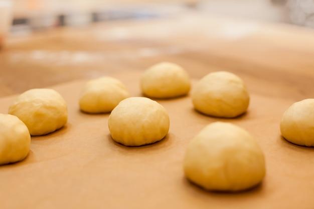 Сырые домашние булочки на кухонном столе в процессе приготовления