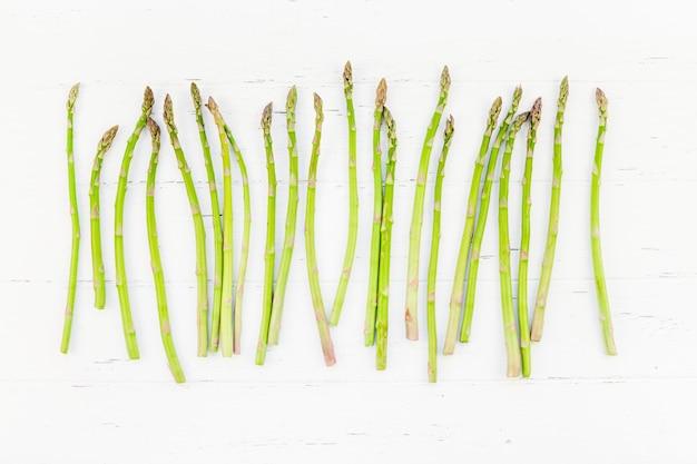 白い木製の表面に新鮮なグリーンアスパラガス