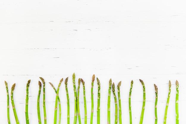 Свежая зеленая спаржа на белой деревянной поверхности