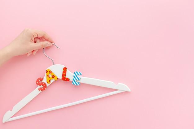 ピンクの背景の販売テキストと白いハンガー