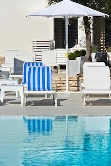 Лежаки и зонтики у бассейна в солнечный день