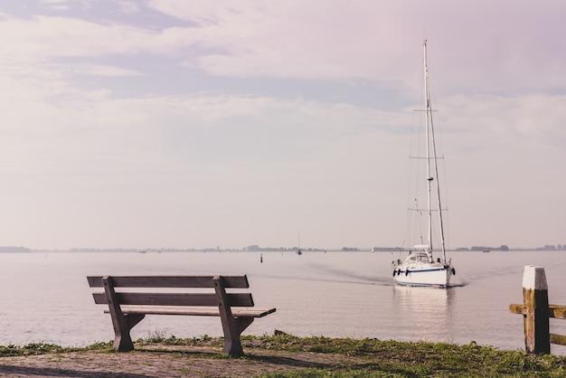 Живописный вид на море со скамейкой и парусником