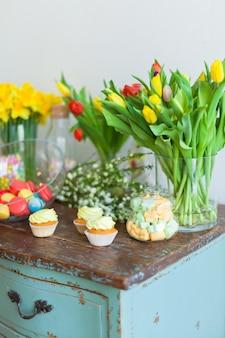 明るいマカロンと木製のテーブルのカップケーキ