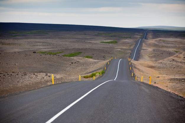 Живописный вид в мрачную погоду бесконечного исландского шоссе
