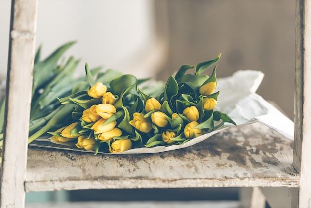 木製のテーブルの上の黄色いチューリップの花の花束