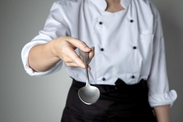 キッチンレストランで料理を準備するシェフの手のスプーンの料理はおいしい味をしたい