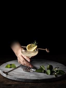 Рука держать стеклянный коктейль шейкер ситечко на деревянном фоне с копией пространства