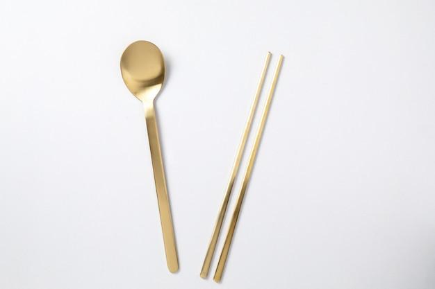 Золотая ложка палочки в корейском стиле на белом