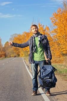 バックパックで若いひげを生やしたヒップスターヒッチハイカーが秋の道路で車をキャッチしようとしました。