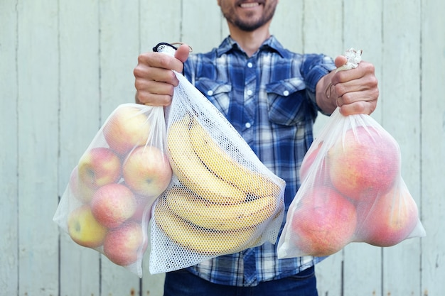 廃棄物ゼロのショッピングコンセプト。新鮮な果物と再利用可能なエコバッグを持って笑みを浮かべて男。使い捨てプラスチックの禁止