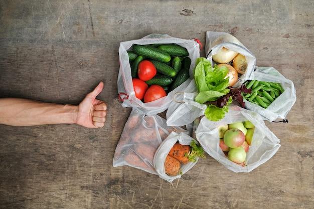 再利用可能なメッシュバッグに入れられた新鮮な有機野菜、果物、緑、および人間の手の指差しサイン。廃棄物ゼロのショッピングコンセプト。使い捨てプラスチックなし