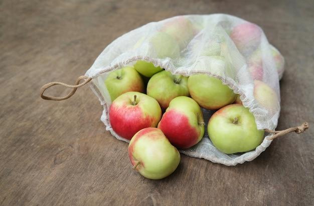 Ноль отходов, концепция покупок. свежие органические яблоки в сетке многоразового использования производят мешок на деревянном столе