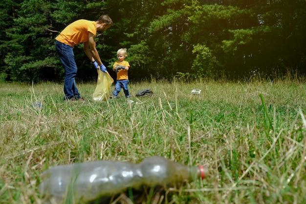 Отец и его маленький сын собирают мусор и пластиковые бутылки в парке. семья добровольцев собирает мусор в лесу. концепция охраны окружающей среды