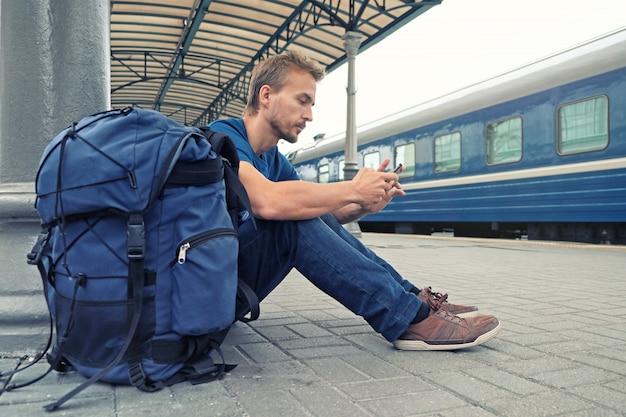 若者を生やしたスマートフォンと鉄道駅のプラットフォームの上に座って、電車を待っているバックパックと男の観光客。旅行のコンセプト