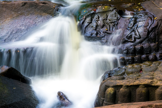 彫刻が施された像を流れる滝