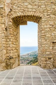 海の景色と古い城の遺跡の中で古代の窓