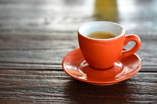 Закройте вверх по оранжевой кофейной чашке на черной деревянной таблице около окна на кафе.