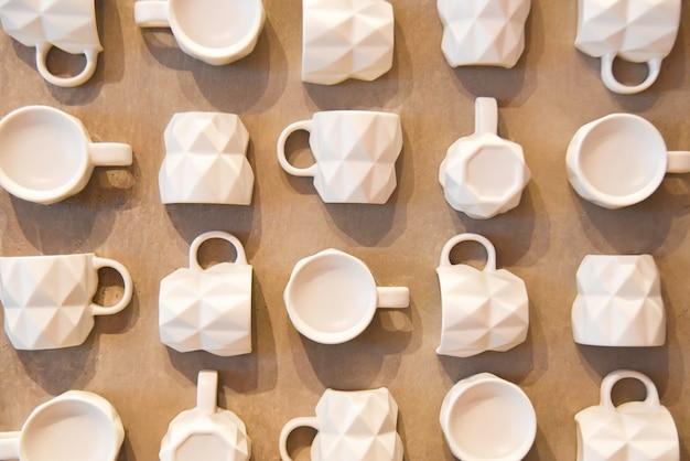 木製の壁に多くの白いカップ
