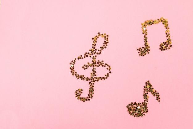 ピンクのパステルの背景に横たわる星空の黄色の紙吹雪のミュージカルノート。