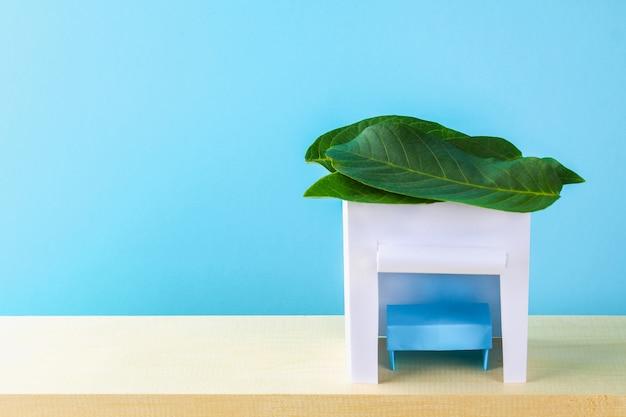 ハッピースコット。青い背景に葉で覆われた紙の小屋。スペースをコピーします。