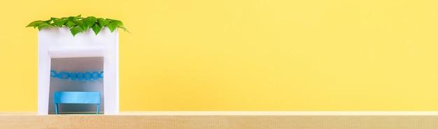 バナー。ハッピースコット。黄色の背景に葉で覆われた紙の小屋。コピー