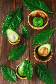 緑の生の完熟カットとアボカド果実全体を石で木製のボウル