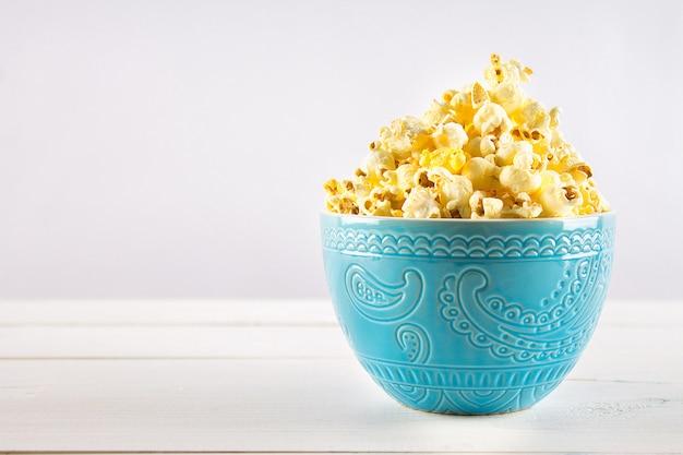 Соленый попкорн в синей чашке находится на деревянном столе.