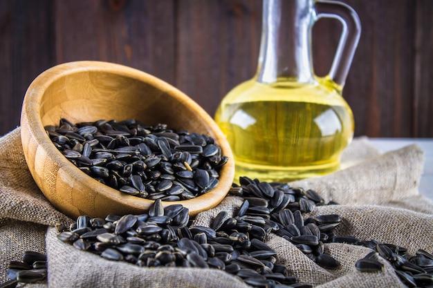 ひまわりの種と木製のテーブルの上の油。