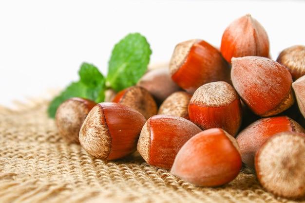 Орехи фундука разбросаны на вретище на белом деревянном столе.