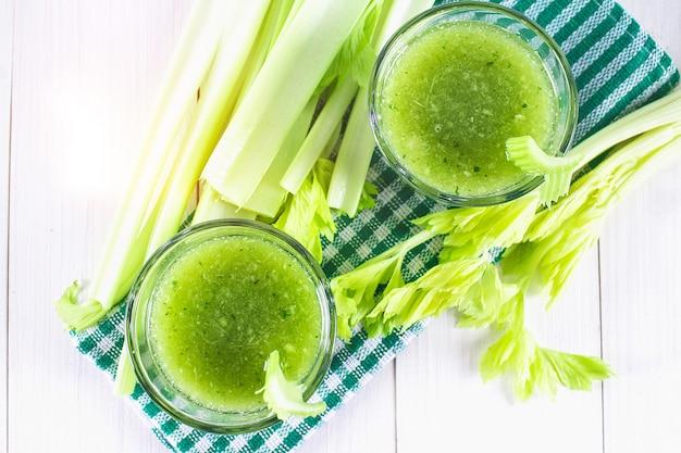 セロリの葉、白い木製の背景に健康的なライフスタイルから作られた野菜のカクテル。
