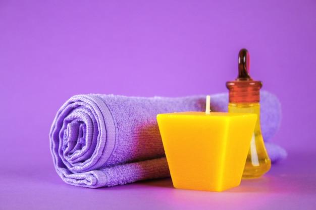 黄色のろうそくとアロマオイル、紫色の背景に紫色のタオル。スパ。