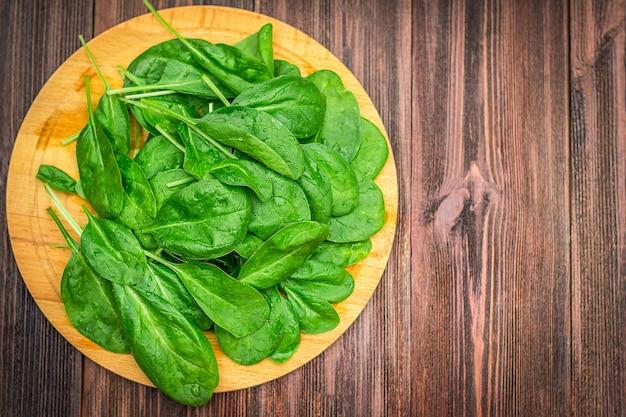 新鮮なジューシーなほうれん草は木製の茶色のテーブルに残します。天然物、野菜、健康食品
