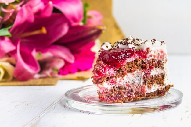 ケーキと白い木製のテーブルの上の花の花束。
