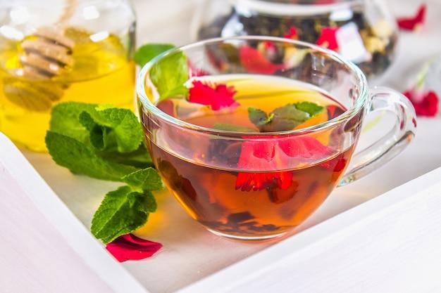 カップの花茶、蜂蜜の瓶、瓶の中の茶、ベッドの中の白い皿の上に。