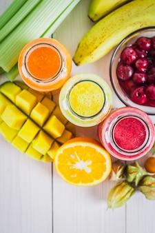 Разноцветные смузи в бутылках из манго, апельсина, банана, сельдерея, ягод, на деревянном столе.