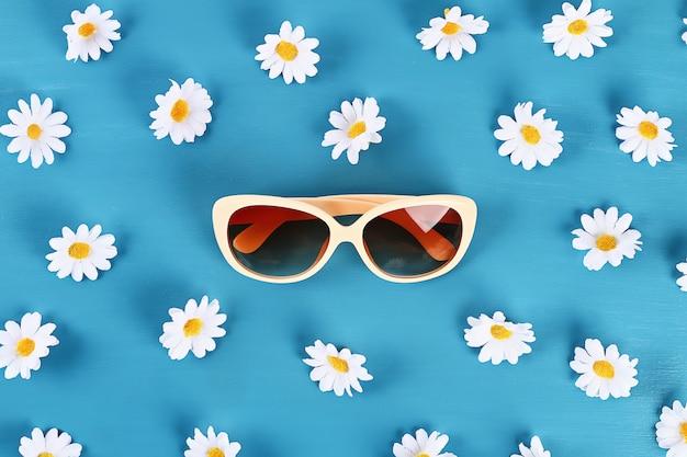 Солнцезащитные очки и ромашки на синем фоне.