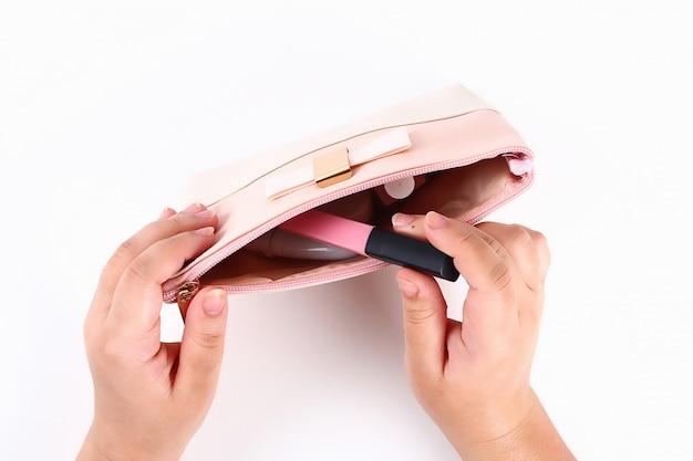 女の子は白の化粧品袋から化粧品を取り出します。上面図。
