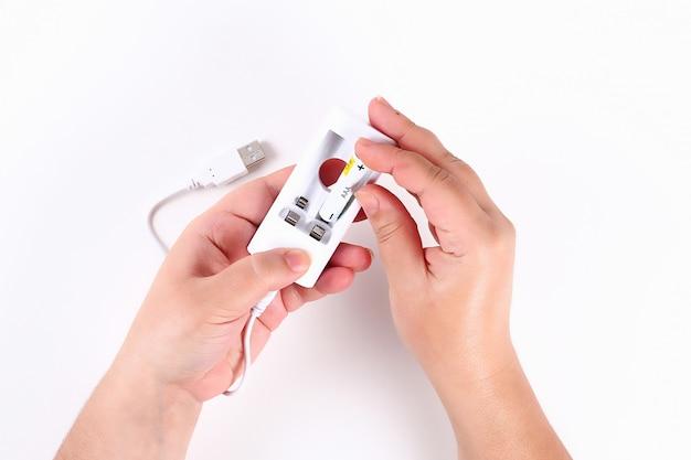 Девушка заряжает аккумулятор в экологии аккумулятора, перерабатывает.