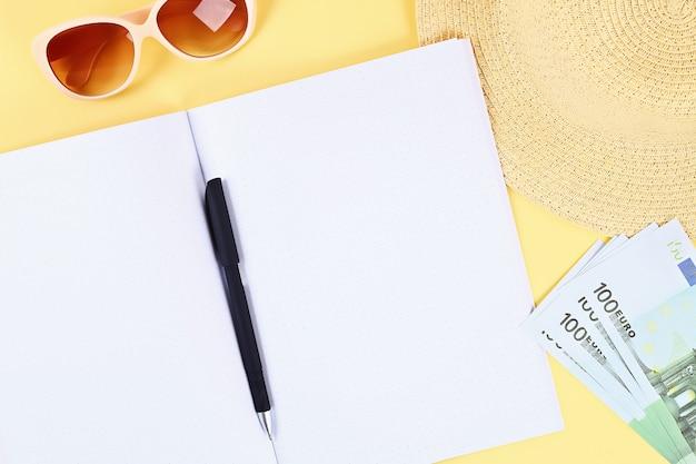 黄色の背景上のノートブック。夏のコンセプトです。休暇のための準備