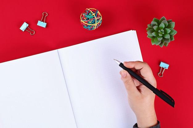 赤いテーブル、植物、ペンに空白のメモ帳。トップビュー、フラットレイアウト。モックアップ、スペースをコピーします。