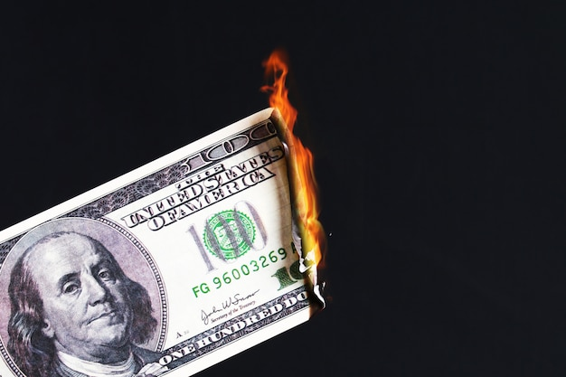 火の炎で燃える百アメリカドル。ドルの崩壊。切り下げ。下落通貨