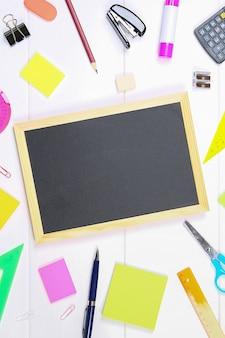白い木製のテーブルのひな形に囲まれた黒板。スペースをコピーします。