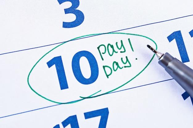 Концепция выплаты жалованья. бизнес, финансы, сбережения денег. календарь с маркером круга в день выплаты жалованья