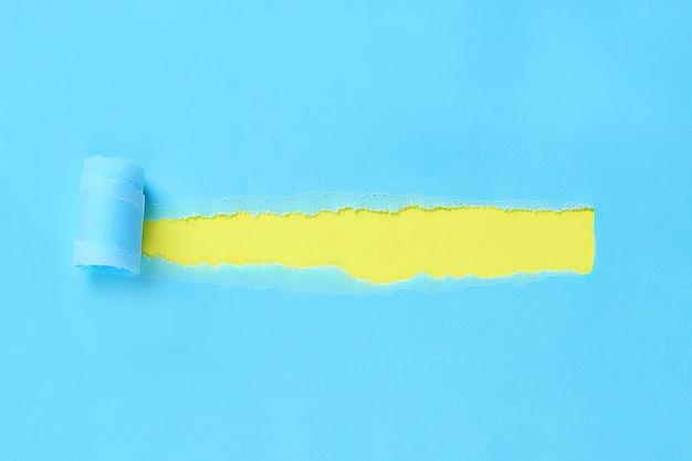 メッセージ用のスペースと引き裂かれた色の包装紙。背景の紙に穴をリッピングしました。コピースペース