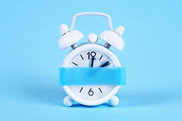 白い目覚まし時計パステルブルーの背景。クロックに空白の付箋。スペースコピー。最小限のコンセプト。